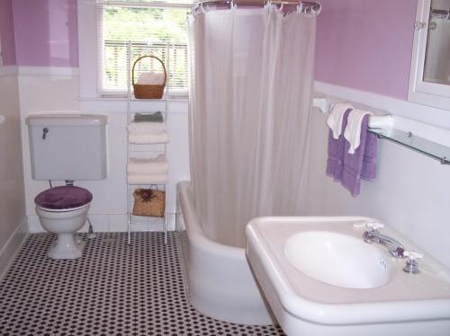 Угловая ванная в маленькой комнатке в фиолетово-белом дизайне